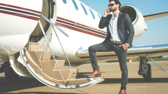 Well dressed businessman with sunglasses talking over mobile phone while standing on the steps ofprivate jet airplane.