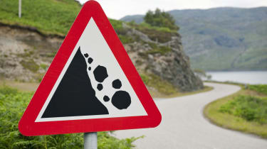 There may be trouble ahead - a rural road sign warning of a danger of falling rocks around the corner on a road in Scotland.