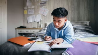 picture of teenager studying on his bed