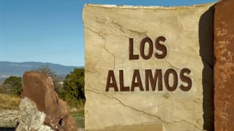 """The hard light of the setting sun casts harsh shadows on this carved and painted stone sign at the entrance to the town of Los Alamos, New Mexico, home to the Los Alamos National Laboratory,"