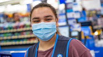 A Walmart employee wearing a COVID mask looks into the camera