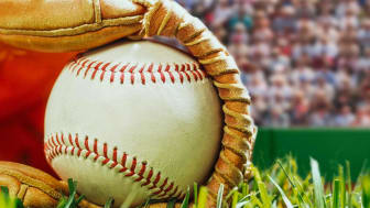 A baseball in a glove on the ground of a baseball field