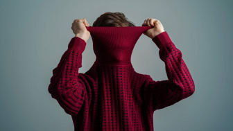 A person pulls the neck of a turtleneck up over their face.