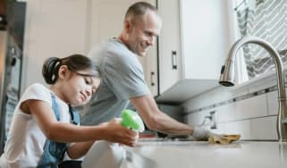 A dad and his little girl clean the kitchen together.