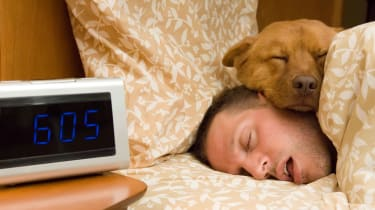 A sleeping man snores while his dog sleeps on top of him.