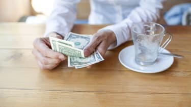 woman with white shirt ready to pay empty finished cappuccino coffee cup with dollar banknotes in hand on light brown wooden table cafe