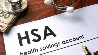 Paper with wordshealth savings account (HSA) on a table.