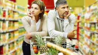 A couple looks frustrated while looking for items in a grocery store aisle