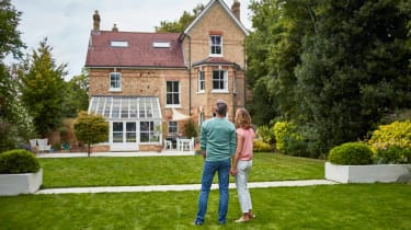 A couple look wistfully at a large brick home.