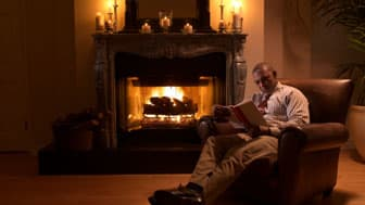 Mature man reading by fire