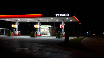 Cross Hands, UK - September 10, 2014: Forecourt of Texaco petrol station at night. The cashier is visible through teh window