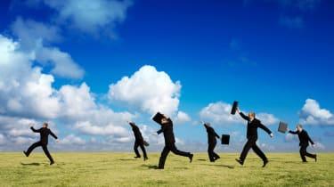 Men in suits run across a field.