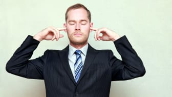 A businessman, with eyes closed, puts his fingers in his ears.