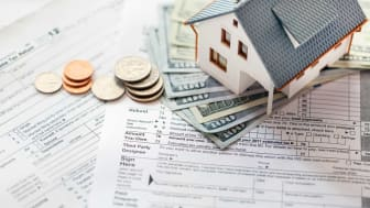 picture of money and a small model house on some tax forms
