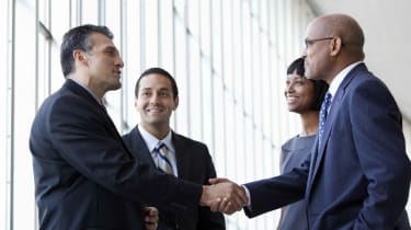 Businesspeople close a deal by shaking hands