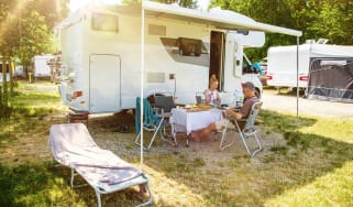 Retired couple reading outside their RV in an RV park