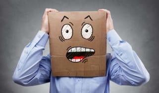 Man with a box on his head painted with a worried face