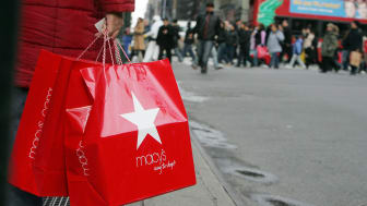 NEW YORK - DECEMBER 27:A post-Christmas shopper holds Macy's bags as other shoppers cross Seventh Avenue December 27, 2006 in New York City. Retailers are hoping that after-Christmas shoppers