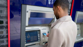 Portrait of a business man withdrawing money from an ATM - financial concepts. Interface on screen was designed from scratch by us.