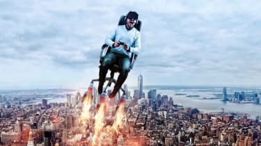 A man in a gaming chair with VR goggles rockets through the air above a city