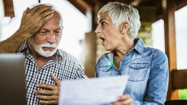 picture of senior couple shocked by what they see on a piece of paper
