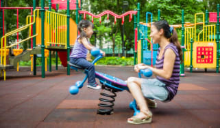 Lovely toddler girl playing seesaw with pretty young mom at the playground joyfully.