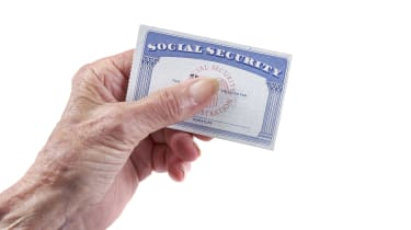 A hand holding a Social Security card