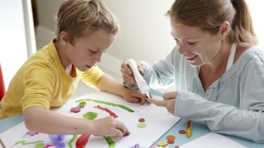 Child, aged 6-7, and woman, aged 33, sticking buttons on a picture together in a family kitchen.