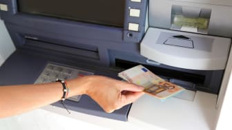 woman while withdrawing banknotes 50 euros from an ATM in europe