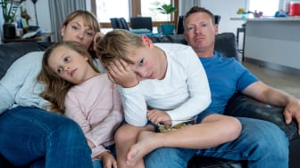 picture of a grumpy family sitting on their couch at home