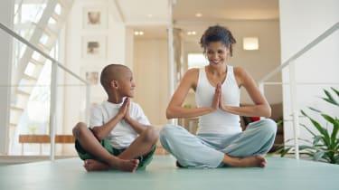 A mom teaches her son how to do yoga.