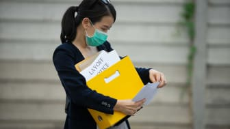 A woman carrying an armload of papers looks at her layoff notice