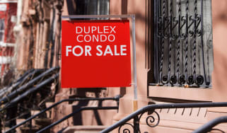 A for sale sign in front of a duplex