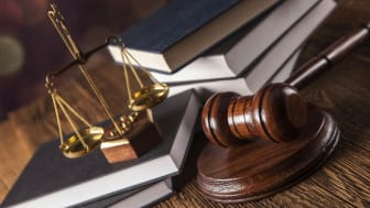 Books, a gavel, and a scales of justice on a desk.