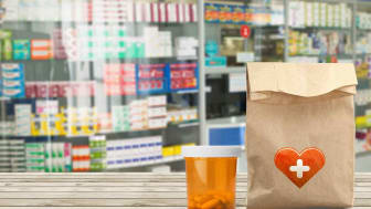 A bottle of pills, a bag with prescriptions sit on the counter of a pharmacy