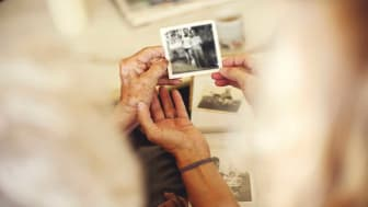 picture of elderly woman looking a old photos of her and her late husband
