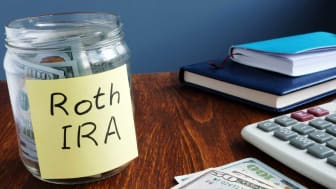 "picture of a jar labeled ""Roth IRA"" with money in it"