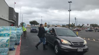 Walmart workers handing out cases of water to drivers