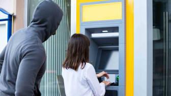 Man in hoodie looking over woman's shoulder at ATM
