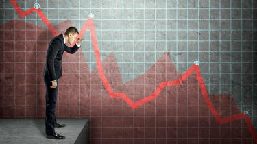 Man looking down against backdrop of negative stock chart