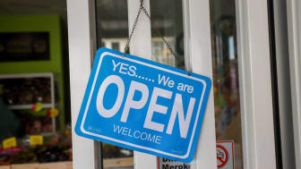 "A sign in a business doorway reads ""open."""