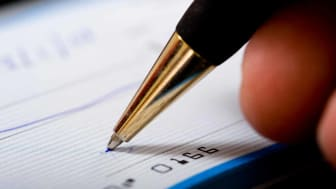 picture of pen writing on a personal check