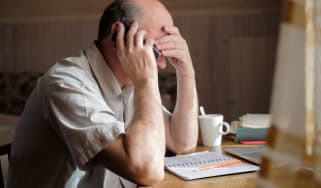 A man is on a telephone while looking stressed