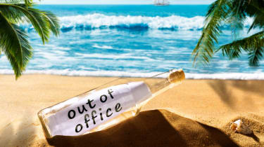 A bottle sitting on a beautiful beach that with a paper inside that says out of office.