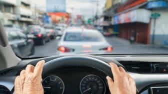 Senior woman driving a car in traffic jam
