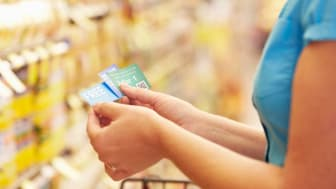 A female shopper looks at coupons while shopping in a supermarket