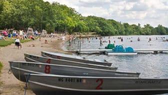 Boats on a beach along with beachgoers