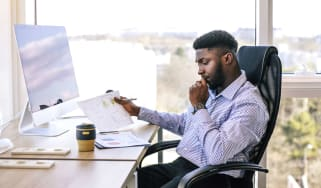 A man sits at a desk and looks at investment documents.