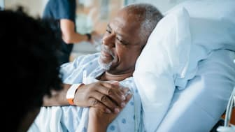 Nurse comforting a senior medical patient in a hospital bed