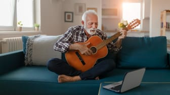 A man sits on his couch and plays the guitar.
